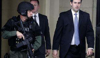 FILE- In this Dec. 5, 2016 file photo, Michael Slager, at right, walks from the Charleston County Courthouse under the protection from the Charleston County Sheriff's Department after a mistrial was declared for his trial in Charleston, S.C.  Attorneys have asked an appellate court to reconsider its ruling upholding the conviction and 20-year sentence of Slager,, a former South Carolina policeman in the shooting death of an unarmed motorist who was running away from a traffic stop.  (AP Photo/Mic Smith, File)