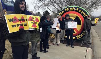 In this Tuesday, Jan. 22, 2019 photo, Brendan Shaughnessy, left, with the Nuclear Issues Study Group, protests with other activists ahead of a meeting of a U.S. Nuclear Regulatory Commission panel in Albuquerque, N.M. Environmentalists and nuclear watchdog groups are lining up against plans to build a $2.4 billion storage facility in southeastern New Mexico for spent nuclear fuel from commercial reactors around the United States(AP Photo/Susan Montoya Bryan)