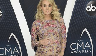 FILE - In this Nov. 14, 2018 file photo, Carrie Underwood arrives at the 52nd annual CMA Awards in Nashville, Tenn. Underwood and husband Mike Fisher announced the birth of their second son, Jacob Bryan Fisher, in a post on Instagram. The 35-year-old singer posted photos of the newborn, who she said was born early Monday, Jan. 21. (Photo by Evan Agostini/Invision/AP, File)