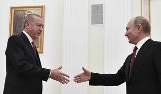 Russian President Vladimir Putin, right, greets Turkey's President Recep Tayyip Erdogan prior to their talks in the Kremlin in Moscow, Russia, Wednesday, Jan. 23, 2019. (Alexander Nemenov/Pool Photo via AP)