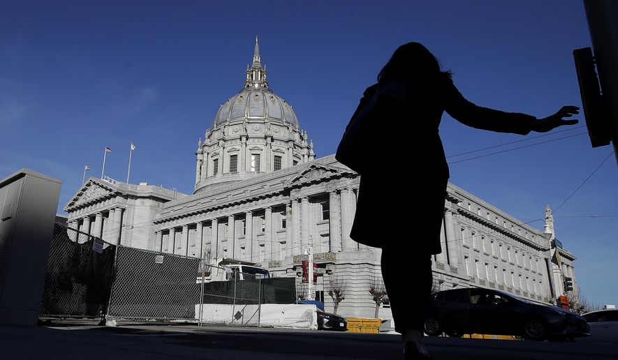 A woman waits to cross the street in front of City Hall in San Francisco, Wednesday, Jan. 23, 2019. In an apparent exception to its sanctuary protections, officials agreed on Wednesday to work with federal authorities to extradite a felony rape suspect from Canada. (AP Photo/Jeff Chiu)