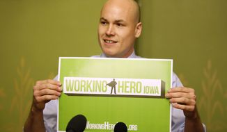 Former Iowa Democratic Congressional candidate J.D. Scholten holds up a sign as he speaks during a news conference, Wednesday, Jan. 23, 2019, at the Statehouse in Des Moines, Iowa. Scholten, a former minor league baseball player who narrowly lost his bid to defeat U.S. Rep. Steve King in Iowa's 4th Congressional District says he's keeping his options open for a political future but for now is working to create an Iowa nonprofit organization to help fight poverty.  (AP Photo/Charlie Neibergall)