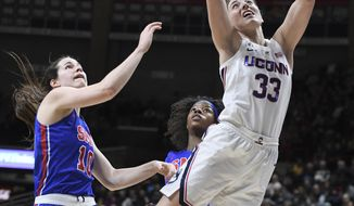 Connecticut's Katie Lou Samuelson shoots next to SMU's Alicia Froling, left, and Kayla White during the first half of an NCAA college basketball game Wednesday, Jan. 23, 2019, in Storrs, Conn. (AP Photo/Jessica Hill)