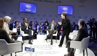 """Singer and co-founder of RED Bono, 2nd right, gestures to Afsaneh Mashayekhi Beschloss, founder of RockCreek, Christine Lagarde, Managing Director of IMF and Rwanda President Paul Kagame, from left, as he arrives for the """"Closing the Financing Gap"""" session at the annual meeting of the World Economic Forum in Davos, Switzerland, Wednesday, Jan. 23, 2019. (AP Photo/Markus Schreiber)"""