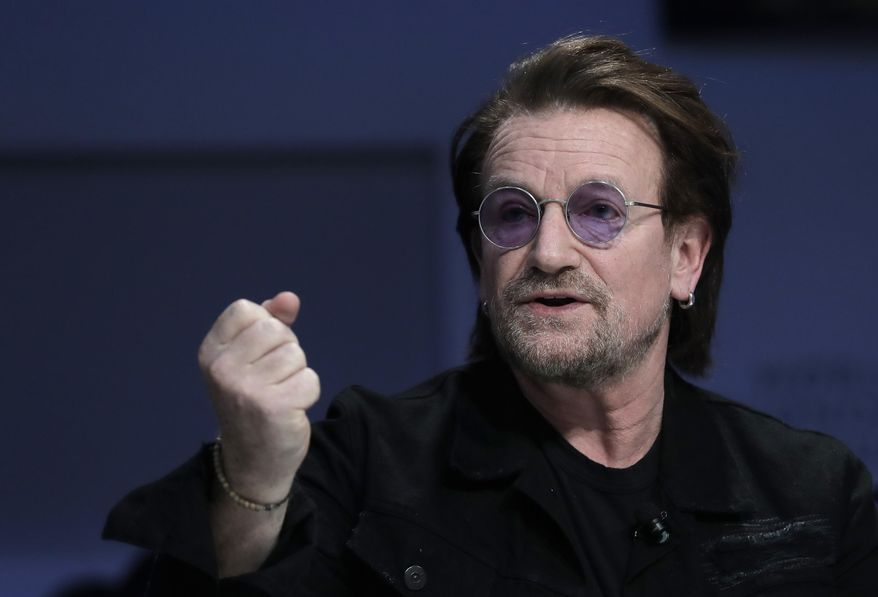 """Singer and co-founder of RED Bono gestures while participating in the """"Closing the Financing Gap"""" session at the annual meeting of the World Economic Forum in Davos, Switzerland, Wednesday, Jan. 23, 2019. (AP Photo/Markus Schreiber)"""