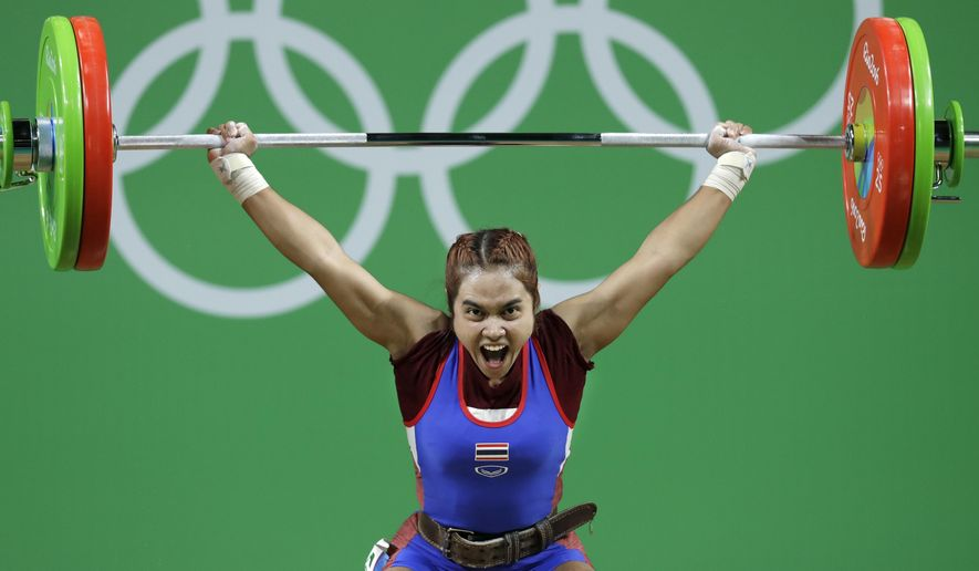 FILE - In this Saturday, Aug. 6, 2016 file photo, Sopita Tanasan of Thailand, competes in the women's 48kg weightlifting competition at the 2016 Summer Olympics in Rio de Janeiro, Brazil. Tanasan won the gold medal. Olympic gold medalist Sopita Tanasan with two world champion weightlifters are among four Thai weightlifters to test positive for banned steroids, the International Weightlifting Federation announced on Tuesday Jan. 22, 2019. (AP Photo/Mike Groll, File)