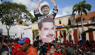 "A supporter of Venezuela's President Nicolas Maduro carries a ""Yankee Go Home"" sign with images of Venezuela's late President Hugo Chaves and Maduro, at Miraflores presidential palace in Caracas, Venezuela, Wednesday, Jan. 23, 2019. At a competing rally, opposition leader Juan Guaido declared himself interim president until new elections can be held, to which Maduro responded by cutting off diplomatic relations with the United States and said American diplomats had 72 hours to leave the country. (AP Photo/Ariana Cubillos)"