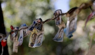 Discontinued Venezuelan bank notes hang above a cigarette stand in the San Jose del Avila neighborhood in Caracas, Venezuela, Tuesday, Jan. 22, 2019. Working class neighborhoods in Venezuela's capital sifted through charred rubble and smoldering trash on Tuesday, following a day of isolated protests in response to the arrest of National Guardsmen who mounted an uprising against President Nicolas Maduro. (AP Photo/Fernando Llano)