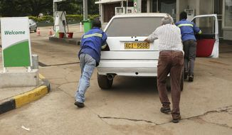 A motorist is helped to push his car into a garage after it ran out out of fuel, in the capital Harare, Wednesday, Jan, 23, 2019. The Southern African nation remained tense as President Emmerson Mnangagwa's call for national dialogue is met with skepticism, and reports of abuses by security forces continued. (AP Photo/Tsvangirayi Mukwazhi)