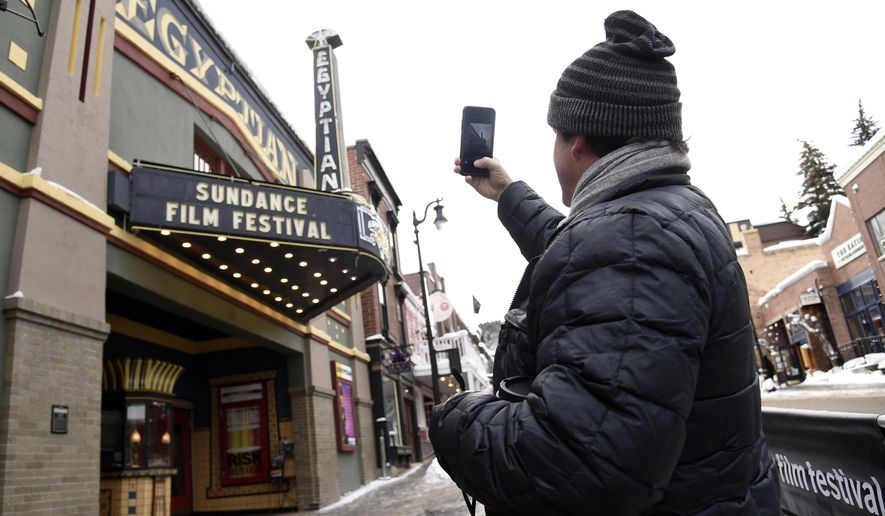 """Matt Arnett of Atlanta, Ga, producer of the Sundance Film Festival narrative short """"I Snuck Off the Slave Ship,"""" takes a picture of the Egyptian Theatre marquee on the first day of the 2019 Sundance Film Festival, Thursday, Jan. 24, 2019, in Park City, Utah. The annual film festival runs through February 3. (Photo by Chris Pizzello/Invision/AP)"""