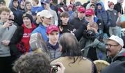 """In this Friday, Jan. 18, 2019, file image made from video provided by the Survival Media Agency, Nick Sandmann, wearing a """"Make America Great Again"""" hat, center left, stands in front of Native American elder Nathan Phillips. (Survival Media Agency via AP)"""