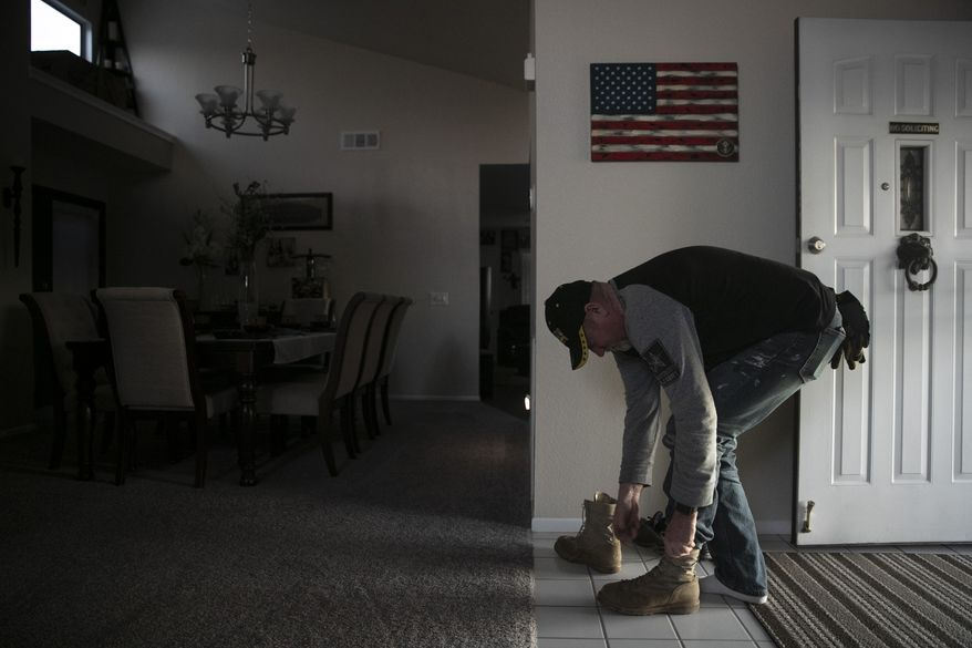 "Chris George, a federal employee furloughed from his job as a forestry technician supervisor for the U.S. Department of Agriculture Forest Service, takes off his boots at his home adorned with an American flag after spending the day working as a handyman Saturday, Jan. 19, 2019, in Hemet, Calif. ""I have a lot of pride, so asking for help is difficult for me. It's very difficult for me because I'm always the one giving back or putting myself before anybody else,"" said George. ""Now, here I am in the situation where I'm the one that is in need."" (AP Photo/Jae C. Hong)"