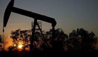 FILE - In this Feb. 19, 2015 file photo, the sun sets behind an oil well in a field near El Tigre, a town within Venezuela's Hugo Chavez oil belt, formally known as the Orinoco Belt. Venezuelan oil exports to the U.S. have declined steadily over the years, falling particularly sharply over the past decade as its production plummeted amid its long economic and political crisis. (AP Photo/Fernando Llano, File)
