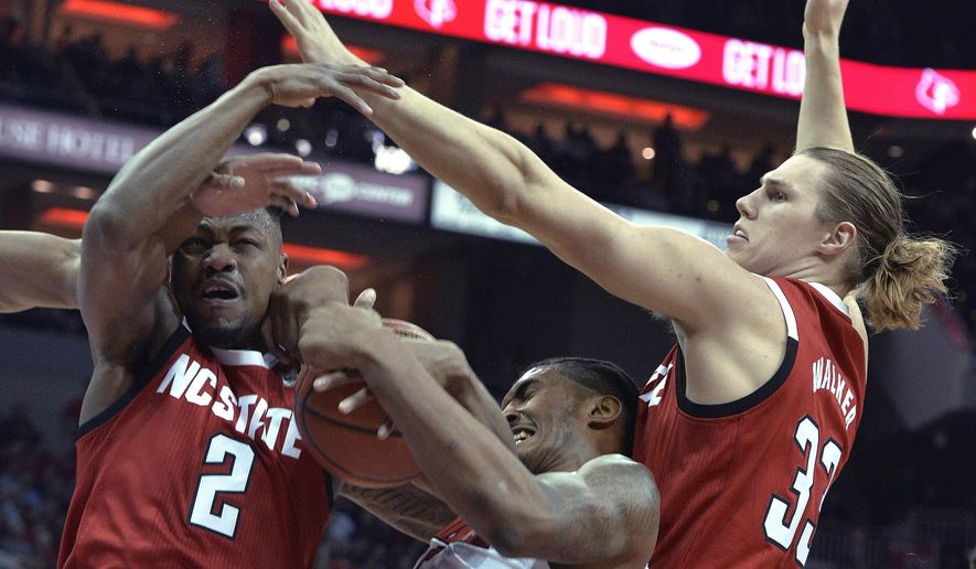 Louisville center Malik Williams and North Carolina State guard Torin Dorn (2) and forward Wyatt Walker (33) battle for a rebound during the first half of an NCAA college basketball game in Louisville, Ky., Thursday, Jan. 24, 2019. (AP Photo/Timothy D. Easley)