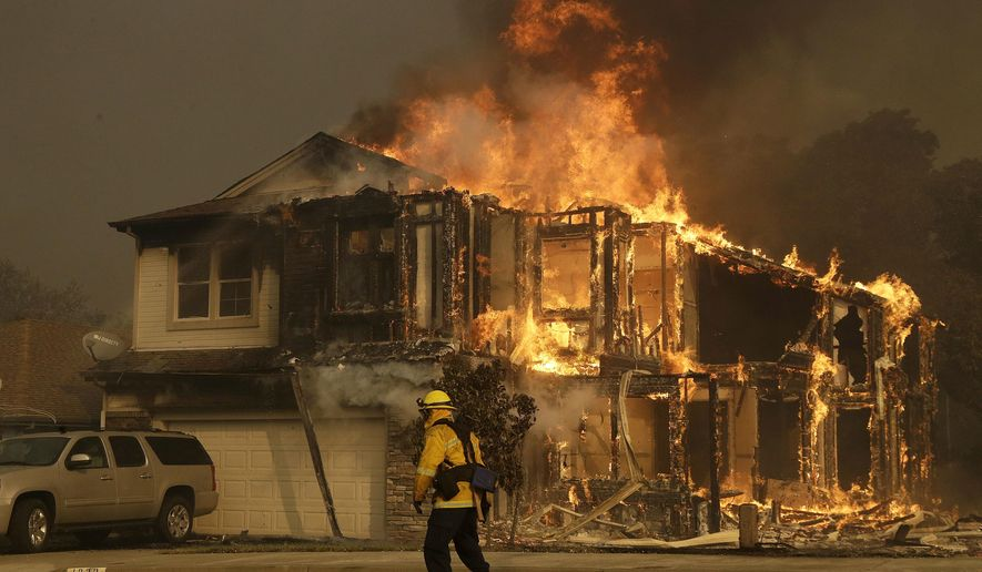 FILE - In this Oct. 9, 2017, file photo, a firefighter walks near a flaming house in Santa Rosa, Calif. Investigators say the deadly 2017 wildfire that killed 22 people in California's wine country was caused by a private electrical system, not embattled Pacific Gas & Electric Co. The state's firefighting agency said Thursday, Jan. 24, 2019, that the Tubbs Fire started next to a residence. They did not find any violations of state law. (AP Photo/Jeff Chiu, File)