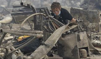 FILE - In this Oct. 9, 2017 file photo, Kristine Pond reacts as she searches the remains of her family's home destroyed by a fire in Santa Rosa, Calif. Investigators say a deadly 2017 wildfire that killed 22 people in California's wine country was caused by a private electrical system, not embattled Pacific Gas & Electric Co. The state's firefighting agency said Thursday, Jan. 24, 2019, that the Tubbs Fire started next to a residence. They did not find any violations of state law. (AP Photo/Jeff Chiu, File)