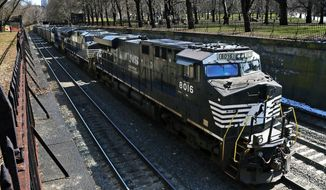 FILE- In this March 26, 2018, file photo, a Norfolk Southern freight train rolls through downtown Pittsburgh. Norfolk Southern Corp. reports financial results Thursday, Jan. 24, 2019. (AP Photo/Gene J. Puskar, File)