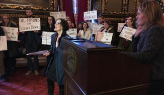 Christina Manning, a professor at Macalaster College, speaks against Enbridge Energy's plan to replace its aging Line 3 crude oil pipeline across Minnesota, at an event organized by Science for the People, in the governor's office at the state Capitol, on Thursday, Jan. 24, 2019, in St. Paul, Minn. At the far right is Kristin Beckmann, Gov. Tim Walz's deputy chief of staff for communications and scheduling. (AP Photo/Steve Karnowski)
