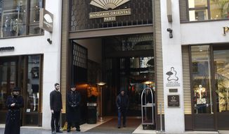 Doormen wait outside the Mandarin Oriental hotel Tuesday Jan.22, 2019 in Paris. U.S. singer Chris Brown and two other people are in custody in Paris after a woman filed a rape complaint, French officials said. The woman who filed the complaint said she met Brown and his friends overnight Jan. 15-16 at the club Le Crystal in the 8th arrondissement near the Champs-Elysees, and then they all went to the Mandarin Oriental Hotel according to the official. (AP Photo/Thibault Camus)