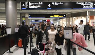 In this Jan. 18, 2019, file photo, Carlos Gonzalez, right, hugs his daughter as she waits in line at a security checkpoint at Miami International Airport in Miami. The strain of a 34-day partial government shutdown is weighing on the nation's air-travel system, both the federal workers who make it go and the airlines that depend on them. Unions that represent air traffic controllers, flight attendants and pilots are growing concerned about safety with the shutdown well into its fifth week.  (AP Photo/Lynne Sladky, File)