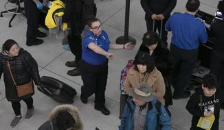 In this Jan. 7, 2019, file photo, a TSA agent, center, directs passengers through a security checkpoint at New York's John F. Kennedy International Airport. (AP Photo/Mark Lennihan, File)