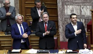 Greece's Prime Minister Alexis Tsipras, right, reacts during a parliament debate about Prespa Agreement in Athens, Thursday, Jan. 24, 2019. Greek lawmakers are debating a historic agreement aimed at normalizing relations with Macedonia in a stormy parliamentary session scheduled to culminate in a Friday vote. (AP Photo/Yorgos Karahalis)
