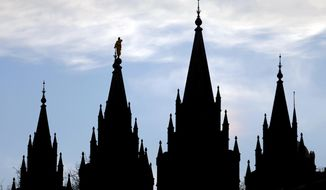 FILE- In this Jan. 3, 2018, file photo, the angel Moroni statue, silhouetted against the sky, sits atop the Salt Lake Temple at Temple Square in Salt Lake City. The Mormon church says it won't oppose strengthening hate-crimes legislation in Utah to include protections for LGBT people. The announcement Thursday, Jan. 24, 2019, could break a longtime legislative logjam. (AP Photo/Rick Bowmer, File)