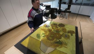 """In this photo taken on Wednesday, Jan. 23, 2019, senior paintings conservator Rene Boitelle works on restoring Vincent van Gogh's world-famous """"Sunflowers"""" painting at the Van Gogh museum in Amsterdam, Netherlands. The painting will remain in the conservation studio for another five weeks to complete the final phase of comprehensive research into the condition of the work. The painting will also be restored in order to ensure that it is preserved for future generations in the best possible manner. (AP Photo/Peter Dejong)"""