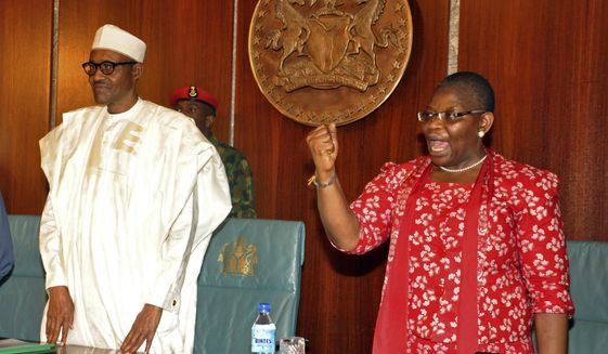FILE - In this Wednesday, July 8, 2015 file photo, Nigerian President Muhammadu Buhari, left, stands next to Oby Ezekwesili, a coordinator of the 'Bring Back Our Girls' campaign, at the presidential residence in Abuja, Nigeria. The woman who led the global campaign to free Nigerian schoolgirls kidnapped by Boko Haram extremists is dropping out of the race for Nigeria's presidency, it was announced Thursday, Jan. 24, 2019. Oby Ezekwesili is the most prominent woman to seek the presidency in Nigeria, where politics, as in many African nations, have long been dominated by men.  (AP Photo/Olamikan Gbemiga, file)
