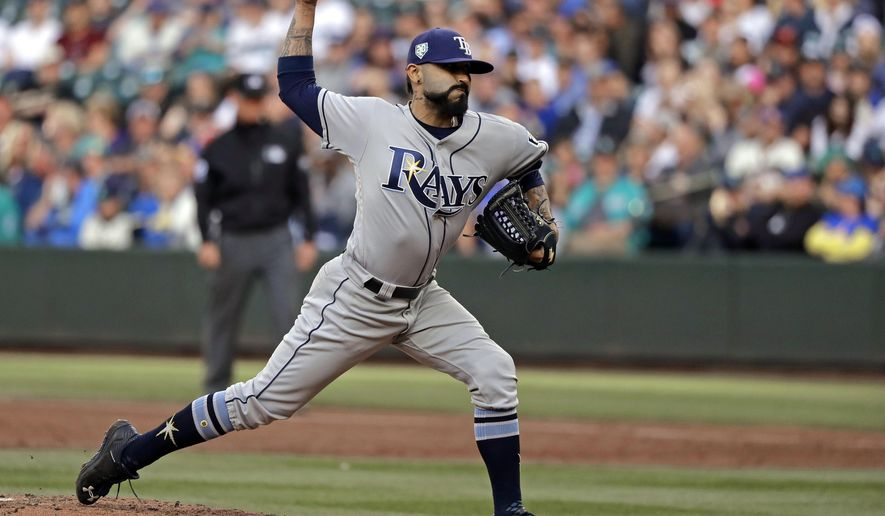 FILE - In this June 1, 2018, file photo, Tampa Bay Rays starting pitcher Sergio Romo throws to a Seattle Mariners batter during the first inning of a baseball game in Seattle. A person familiar with the negotiations tells The Associated Press that Major League Baseball has proposed going back to a 15-day disabled list and increasing the time optioned players usually must spend in the minor leagues. The moves are aimed at reducing the use of relief pitchers and reviving offense. (AP Photo/Ted S. Warren, File)
