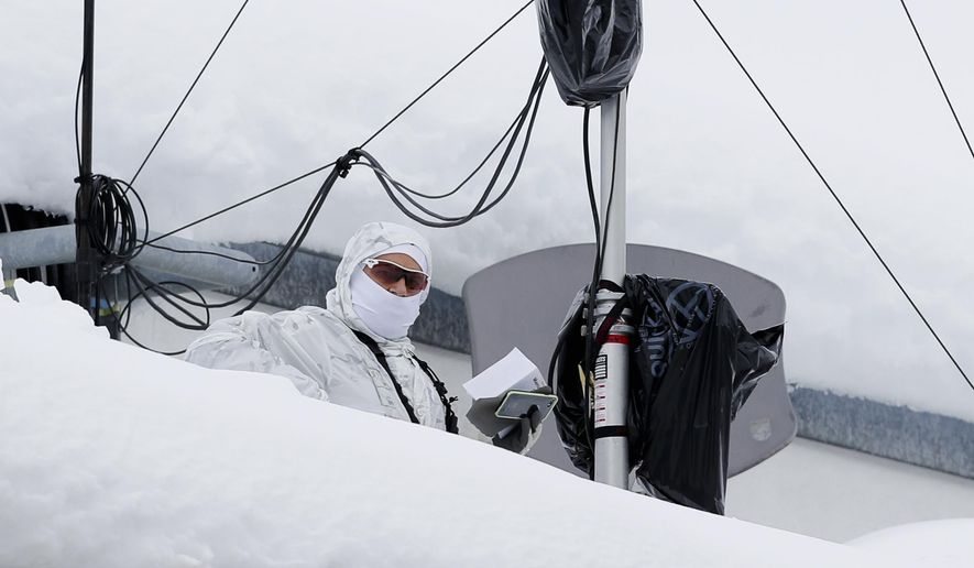 An armed Swiss police officer stands under a security camera system on the roof of the congress center where the annual meeting of the World Economic Forum, WEF, take place in in Davos, Monday, Jan. 21, 2019. (AP Photo/Markus Schreiber)