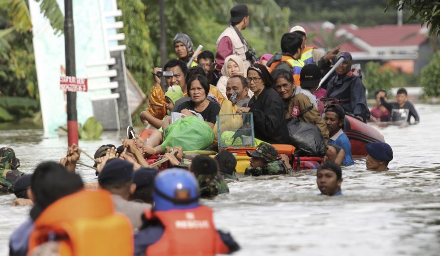 In this Wednesday, Jan. 23, 2019, file photo, residents ride a makeshift raft as they evacuate their flooded homes in Makassar, South Sulawesi, Indonesia. Torrential rains that overwhelmed a dam and caused landslides that killed some and displaced more than a few thousand residents in central Indonesia, officials said Wednesday. (AP Photo/Masyudi Syachban Firmansyah, File)