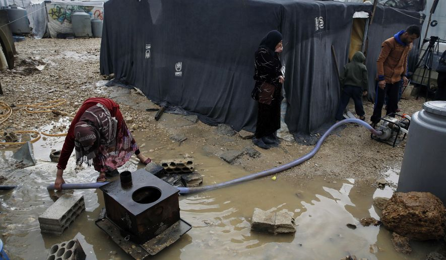 FILE - In this Jan. 3, 2019, file photo, a Syrian refugee family pumps water after heavy rain at a refugee camp in the town of Bar Elias in Lebanon's Bekaa Valley. The World Refugee Council called Thursday, Jan. 24, 2019, for up to $20 billion stolen by government leaders and now frozen in the United States, Britain and other countries to be reallocated by courts to help millions of displaced people forced to flee conflict, persecution and victimization. (AP Photo/Bilal Hussein, File)