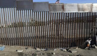 FILE - In this Nov. 21, 2018, file photo, a homeless man walks next to the fence that divides Mexico and the U.S, in Tijuana, Mexico. The Trump administration expects to launch a policy as early as Friday, Jan. 25, 2019, that forces people seeking asylum to wait in Mexico while their cases wind through U.S. courts, an official said, marking one of the most significant changes to the immigration system of Donald Trump's presidency. (AP Photo/Rodrigo Abd, File)