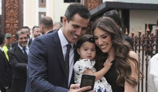 Juan Guaido, left, takes a selfie photo with his wife Fabiana Rosales and his daughter Miranda Guaido upon arrival to swear in the new board of the National Assembly in Caracas, Venezuela. (AP Photo/Fernando Llano, File)