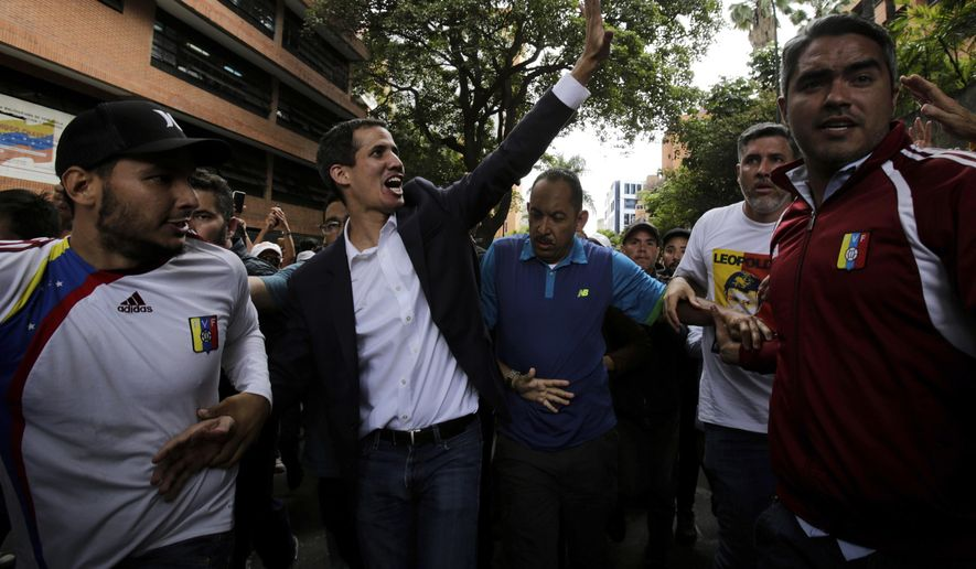 Juan Guaido, head of Venezuela's opposition-run congress, waves at supporters after declaring himself interim president of the South American country, during a rally demanding the resignation of President Nicolas Maduro, in Caracas, Venezuela, Wednesday, Jan. 23, 2019. (AP Photo/Boris Vergara)
