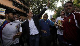 Juan Guaido, head of Venezuela's opposition-run congress, waves at supporters after declaring himself interim president of the South American country, during a rally demanding the resignation of President Nicolas Maduro, in Caracas, Venezuela, Wednesday, Jan. 23, 2019. (AP Photo/Boris Vergara)