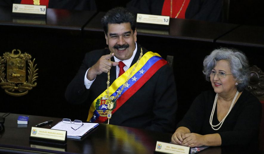 Venezuelan President Nicolas Maduro points to someone in the crowd as he sits inside the Supreme Court for an annual ceremony that marks the start of the judicial year in Caracas, Venezuela, Thursday, Jan. 24, 2019. At right is Tibisay Lucena, president of the National Electoral Council. Venezuelans are heading into uncharted political waters after the young leader of a newly united opposition claimed Wednesday to hold the presidency and Maduro dug in for a fight with the Trump administration. (AP Photo/Ariana Cubillos)
