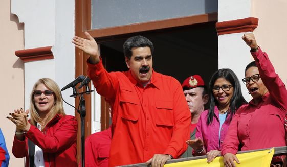 Venezuela's President Nicolas Maduro, center, and first lady Cilia Flores, left, interact with supporters from a balcony at Miraflores presidential palace during a rally in Caracas, Venezuela, Wednesday, Jan. 23, 2019. At a competing rally, opposition leader Juan Guaido declared himself interim president until new elections can be held, to which Maduro responded by cutting off diplomatic relations with the United States and said American diplomats had 72 hours to leave the country. (AP Photo/Ariana Cubillos)