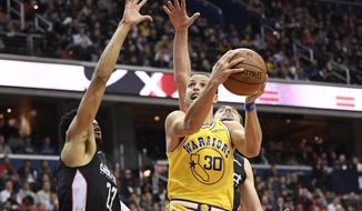 Golden State Warriors guard Stephen Curry (30) goes to the basket against Washington Wizards forward Otto Porter Jr. (22) and guard Tomas Satoransky during the first half of an NBA basketball game Thursday, Jan. 24, 2019, in Washington. (AP Photo/Nick Wass)