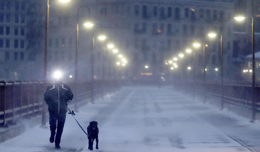 A runner and his dog brave frigid conditions while making their way east across the Stone Arch Bridge Thursday, Jan. 24, 2019, in Minneapolis.   The National Weather Service issued a wind child advisory overnight Thursday for Wisconsin, Minnesota, the Dakotas and several other states where temperatures were expected to plunge to 30 below with the wind as a factor. (David Joles/Star Tribune via AP)