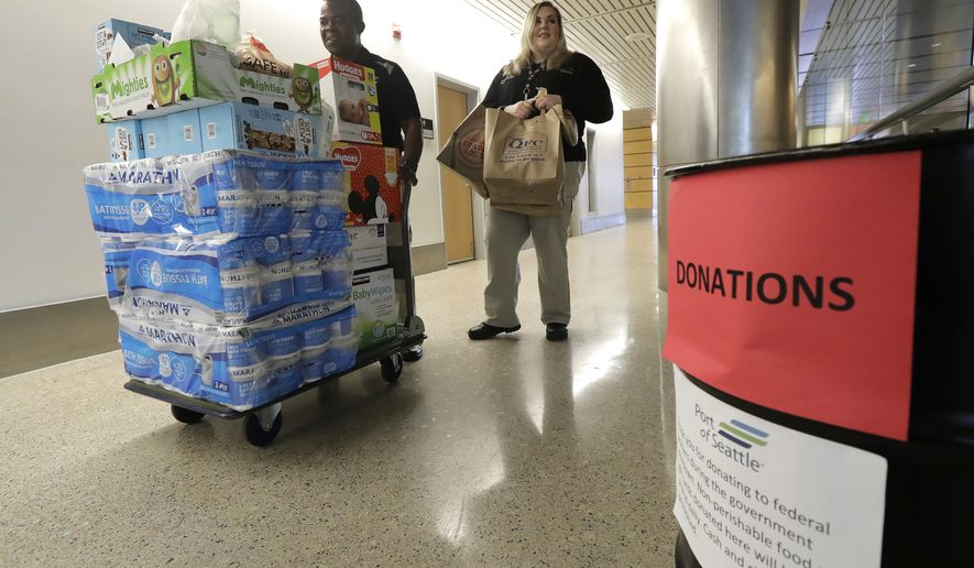 Port of Seattle workers Matondo Wawa, left, and Danica Doyle, right, carry items donated to federal workers affected by the government shutdown at Seattle-Tacoma International Airport down a hallway, Friday, Jan. 25, 2019 in Seattle. The workers said the Port would continue to accept donations despite a short-term deal to reopen the government for three weeks announced Friday by President Donald Trump. (AP Photo/Ted S. Warren)