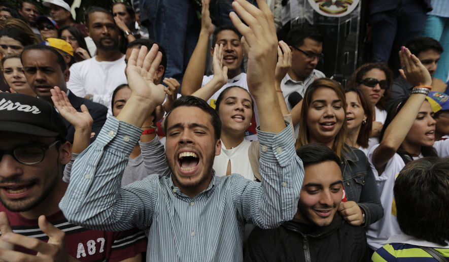 """People shout out against Venezuelan President Nicolas Maduro and """"Guaido President!"""" as they wait for Juan Guaido to arrive at a public plaza where he is expected to speak in Caracas, Venezuela, Friday, Jan. 25, 2019. Guaido is an opposition leader who declared himself interim president on Wednesday. (AP Photo/Fernando Llano)"""