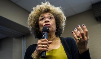 In this Feb. 19, 2015 file photo, Angela Davis speaks during her visit to the University of Michigan-Flint, in Flint, Mich.  An Alabama civil rights museum has reversed course after a public outcry and has decided to give political activist Angela Davis an award that it offered then rescinded. The Birmingham Civil Rights Institute said in a statement Friday, Jan. 25, 2019,  that its board has voted to reaffirm Davis as the recipient of the human rights award.(Jake May/The Flint Journal via AP)