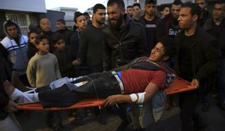 """Palestinian medics wheel a wounded youth, who was shot by Israeli troops during a protest at the Gaza Strip's border with Israel, into the treatment room of Shifa hospital in Gaza City, Friday, Jan. 25, 2019. Israeli troops shot and killed a Palestinian man in Gaza Friday as thousands took part in demonstrations along the border, fueled by Hamas' rejection of Qatari fiscal aid after what the militant group described Israeli delays and """"blackmail."""" (AP Photo/Adel Hana)"""