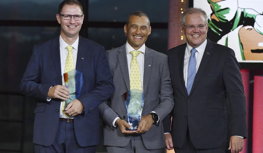 Prime Minister Scott Morrison, right, stands with winners 2019 Australians of the Year; Dr. Richard Harris, left, and Craig Challen at the 2019 Australian of the Year Awards in Canberra, Australia, Friday, Jan. 25, 2019. The two amateur divers Harris and Challen, who canceled their vacation plans for what they thought was a hopeless mission to rescue 12 boys and their soccer coach from a flooded cave in Thailand, have been named winners of one of Australia's most prestigious awards. (Mick Tsikas/AAP Image via AP)