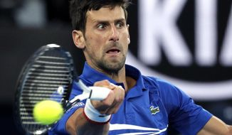Serbia's Novak Djokovic makes a forehand return to Japan's Kei Nishikori during their quarterfinal match at the Australian Open tennis championships in Melbourne, Australia, Wednesday, Jan. 23, 2019. (AP Photo/Aaron Favila)