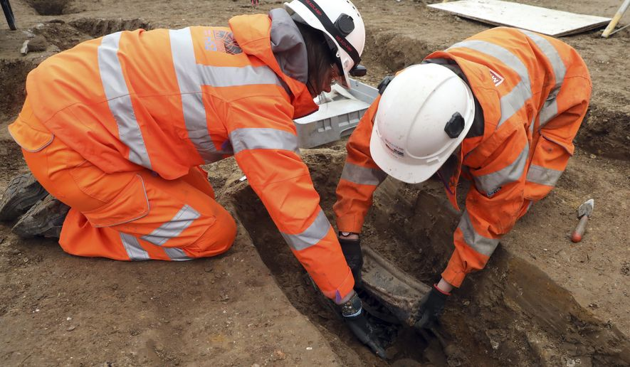 An image taken on Jan. 18, 2019 and issued by HS2 shows archeologists removing the lead plate placed on top of the coffin of Captain Matthew Flinders at the archaeological excavation and research works at St James's Gardens in Euston, London. The remains of Captain Flinders, a noted Royal Navy explorer, who led the first circumnavigation of Australia have been found by archeologists excavating a burial ground where a railway station is planned. The archeologists identified the remains of Flinders by the lead plate placed on top of his coffin. (James O. Jenkins/HS2 via AP)