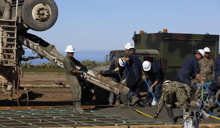 U.S. Marines and Navy Seabees pour fresh concrete as they rebuild the mountaintop runway on storied Santa Catalina Island, Calif., Friday, Jan. 25, 2019. About 100 Marines and sailors began working on the island this month under an agreement with the I Marine Expeditionary Force at Camp Pendleton, California, and the Catalina Island Conservancy. The work on Catalina's Airport in the Sky is paid for by $5 million donated to the nonprofit land trust.(AP Photo/Damian Dovarganes)
