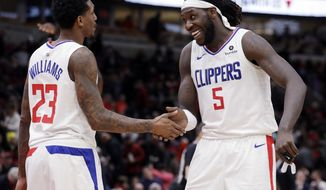 Los Angeles Clippers forward/center Montrezl Harrell, right, smiles as he celebrates with guard Lou Williams after the Clippers defeated the Chicago Bulls 106-101 in an NBA basketball game Friday, Jan. 25, 2019, in Chicago. (AP Photo/Nam Y. Huh)